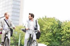Hombres de negocios que hablan mientras que el montar monta en bicicleta al aire libre Fotografía de archivo