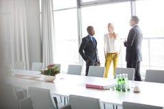 Hombres de negocios que hablan mientras que hace una pausa la mesa de reuniones en oficina Imagen de archivo libre de regalías