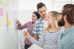 Hombres de negocios que hablan mientras que se coloca en la pared con las notas y los dibujos pegajosos Imagen de archivo