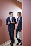 Hombres de negocios que hablan, recorriendo en pasillo de la oficina Imagen de archivo libre de regalías