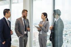 Hombres de negocios que hablan y que discuten planes corporativos fotos de archivo