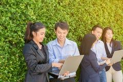 Hombres de negocios que hacen frente a concepto corporativo de la conexión del dispositivo de Digitaces en la pared del árbol Imagen de archivo libre de regalías