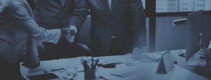Hombres de negocios que hacen frente a concepto corporativo del saludo del apretón de manos fotografía de archivo