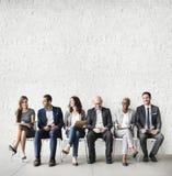 Hombres de negocios que hacen frente a la conexión corporativa del dispositivo de Digitaces concentrada imagen de archivo libre de regalías