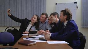 Hombres de negocios que hacen la cara mientras que toma el selfie en oficina