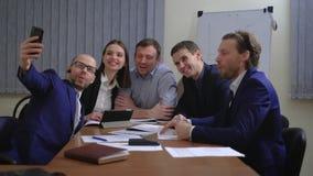 Hombres de negocios que hacen la cara mientras que toma el selfie en oficina almacen de metraje de vídeo