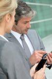 Hombres de negocios que intercambian números Imagenes de archivo