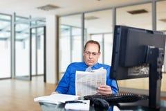 Hombres de negocios que leen el periódico Imagen de archivo libre de regalías