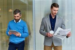 Hombres de negocios que leen en oficina foto de archivo libre de regalías