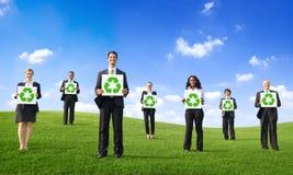 Hombres de negocios que llevan a cabo el cartel con el reciclaje de Sym Foto de archivo libre de regalías