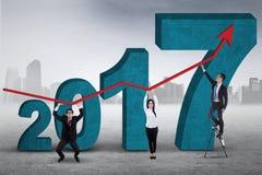 Hombres de negocios que llevan a cabo el gráfico con los números 2017 Imagenes de archivo