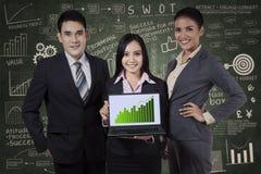Hombres de negocios que llevan a cabo el gráfico del crecimiento Imágenes de archivo libres de regalías