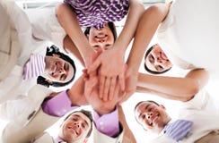 Hombres de negocios que llevan a cabo las manos juntas en un círculo