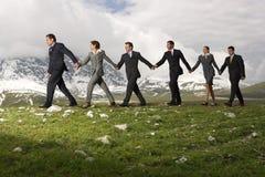 Hombres de negocios que llevan a cabo las manos y que caminan a través de las montañas Fotografía de archivo libre de regalías