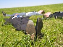 Hombres de negocios que mienten en la hierba Imagenes de archivo