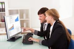 Hombres de negocios que miran cartas de las ventas Fotos de archivo libres de regalías