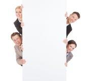 Hombres de negocios que miran de detrás la cartelera en blanco Imágenes de archivo libres de regalías