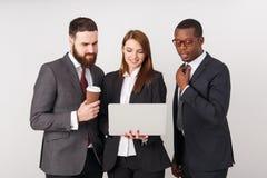 Hombres de negocios que miran el ordenador portátil y la sonrisa foto de archivo libre de regalías