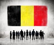 Hombres de negocios que miran la bandera belga Imagen de archivo libre de regalías