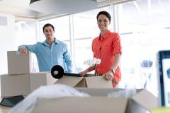 Hombres de negocios que miran la cámara mientras que desempaqueta pertenencia de la oficina de las cajas de cartón en la tabla imagen de archivo