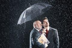 Hombres de negocios que miran la lluvia de debajo el paraguas imagen de archivo
