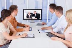 Hombres de negocios que miran los monitores de computadora en oficina Imagen de archivo libre de regalías