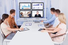 Hombres de negocios que miran los monitores de computadora en oficina Fotos de archivo libres de regalías