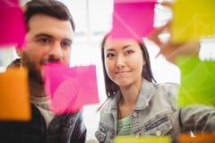 Hombres de negocios que miran notas pegajosas coloreadas multi sobre el vidrio Imagenes de archivo
