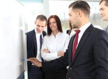 Hombres de negocios que miran a su líder mientras que él que explica algo Imagen de archivo libre de regalías