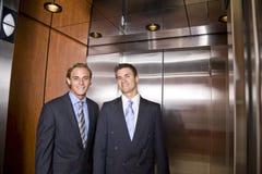 Hombres de negocios que montan en elevador Imagen de archivo libre de regalías
