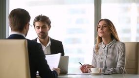 Hombres de negocios que negocian bajo contrato en la reunión de grupo formal almacen de video