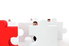 Hombres de negocios que ocultan detrás de rompecabezas Imagen de archivo
