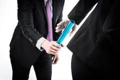 Hombres de negocios que pasan el bastón de la retransmisión imagen de archivo libre de regalías