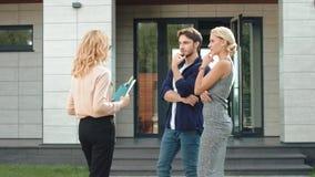 Hombres de negocios que permanecen cerca de casa de lujo Casa de alquiler del hombre y de la mujer junto almacen de video