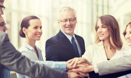 Hombres de negocios que ponen las manos en el top en oficina fotografía de archivo libre de regalías