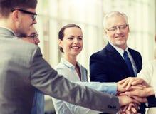 Hombres de negocios que ponen las manos en el top en oficina imágenes de archivo libres de regalías
