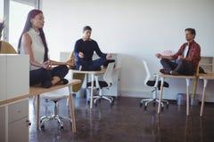 Hombres de negocios que practican yoga en la oficina Imagen de archivo libre de regalías
