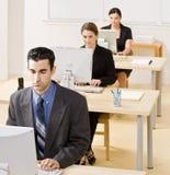 Hombres de negocios que pulsan en el ordenador Imágenes de archivo libres de regalías