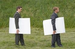 Hombres de negocios que recorren con las hojas del papel Imagen de archivo libre de regalías