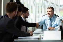 Hombres de negocios que sacuden las manos, acabando para arriba una reunión fotografía de archivo