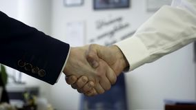 Hombres de negocios que sacuden las manos como muestra del acuerdo Ciérrese para arriba para el apretón de manos firme de dos soc almacen de metraje de vídeo