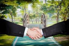 Hombres de negocios que sacuden las manos con un pequeño puente de madera curvado en t Fotografía de archivo libre de regalías