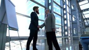 Hombres de negocios que sacuden las manos después de la presentación