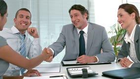 Hombres de negocios que sacuden las manos durante la reunión metrajes