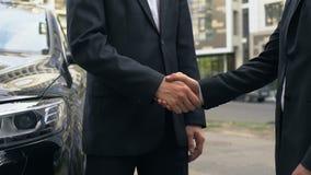 Hombres de negocios que sacuden las manos en el acuerdo, encontrándose al aire libre, cabildeo informal almacen de video