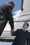Hombres de negocios que sacuden las manos en el campo de aviación Fotos de archivo