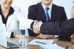 Hombres de negocios que sacuden las manos en el encuentro o la negociación en la oficina Concepto del apretón de manos Satisfacen foto de archivo
