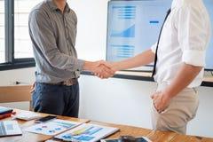 Hombres de negocios que sacuden las manos en la sala de reuni?n, trato acertado despu?s de encontrar imagen de archivo libre de regalías