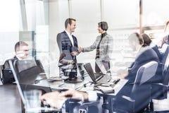 Hombres de negocios que sacuden las manos en oficina corporativa del moder imagen de archivo