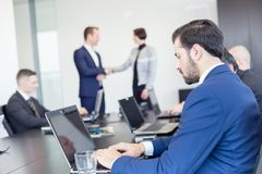 Hombres de negocios que sacuden las manos en oficina corporativa del moder imagenes de archivo